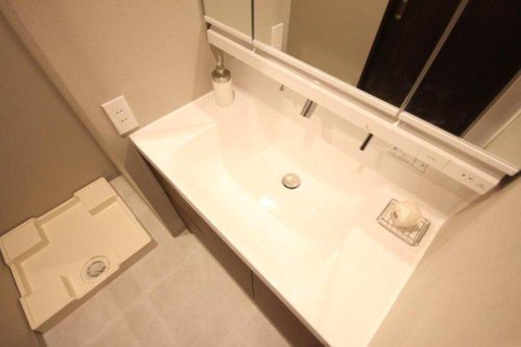 大きく見やすい三面鏡で清潔感ある洗面台は、身だしなみチェックや肌のお手入れに最適です。何かとに物が増える場所だからこそ、スッキリと見映えの良い空間に拵えました。