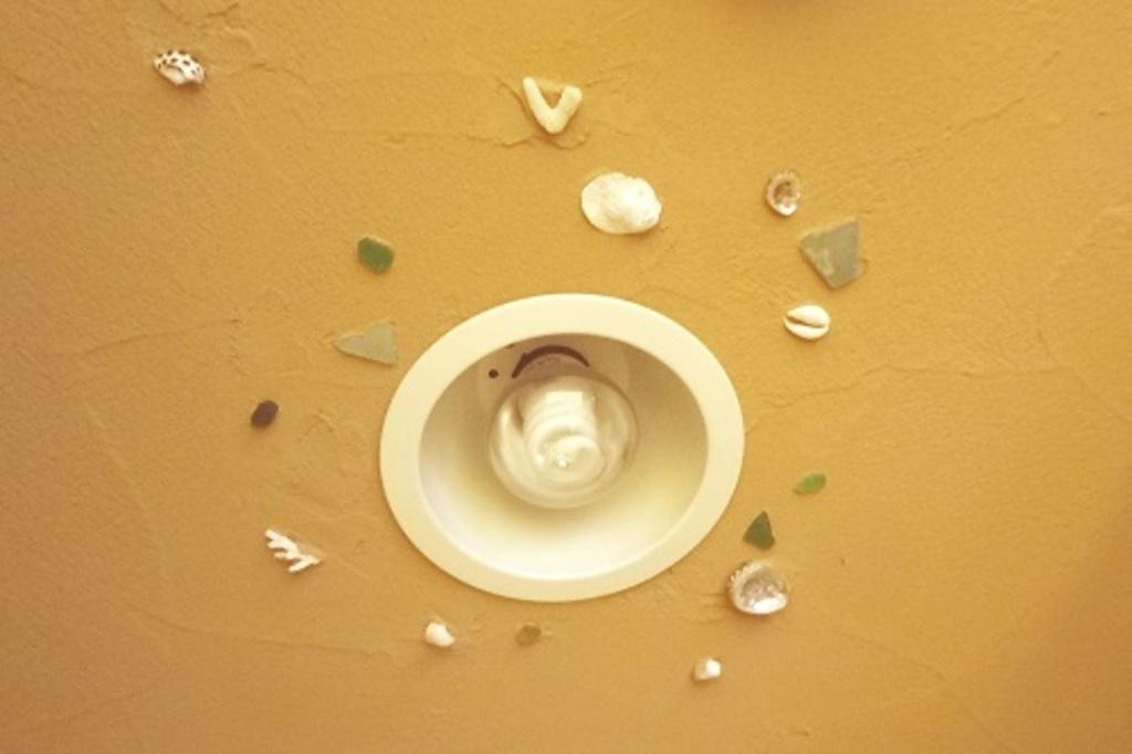 珪藻土で仕上げた照明周りには思い出の貝殻を埋め込んで。